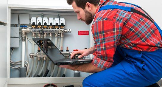 Arbeiter mit Laptop an Klimaanlage